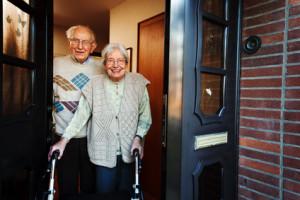 elderly couple opening the front door
